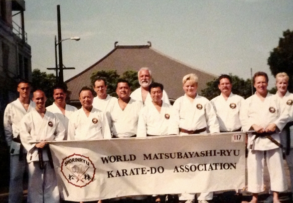 Staging for the Nisei Week Parade at 308 Crocker Street in Los Angeles' Little Tokyo, during the 2000 WMKA World Seminar. Makishi-sensei, Akamine-sensei, and Taira-sensei stand front row, center, as Higashi Honganji Buddhist Temple looms in the background.
